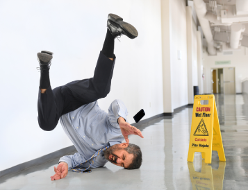 A professional man slips and falls on the wet floor